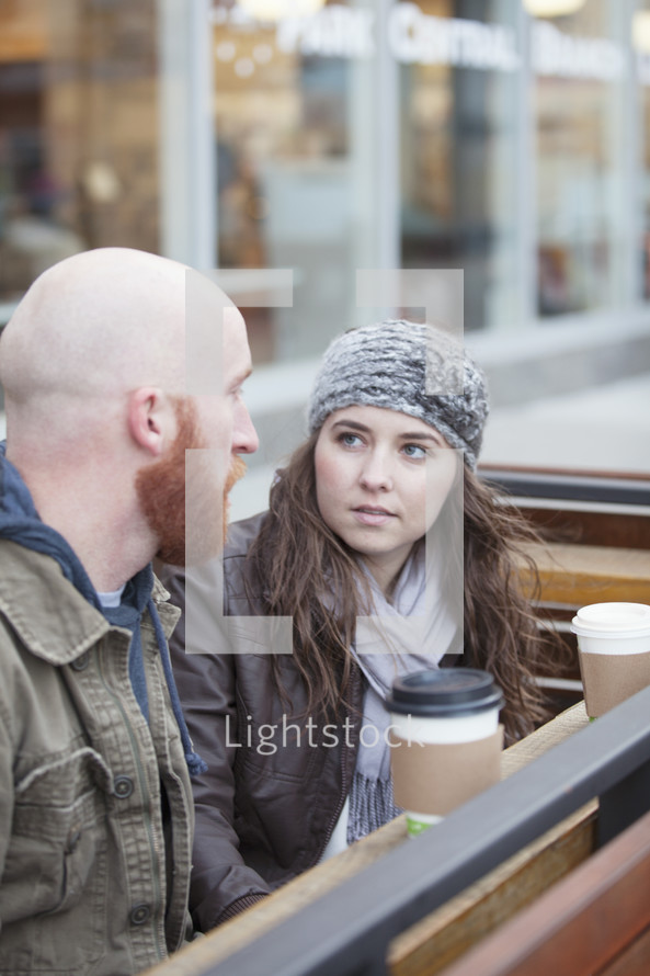 Couple sitting outside with coffee having a serious conversation.