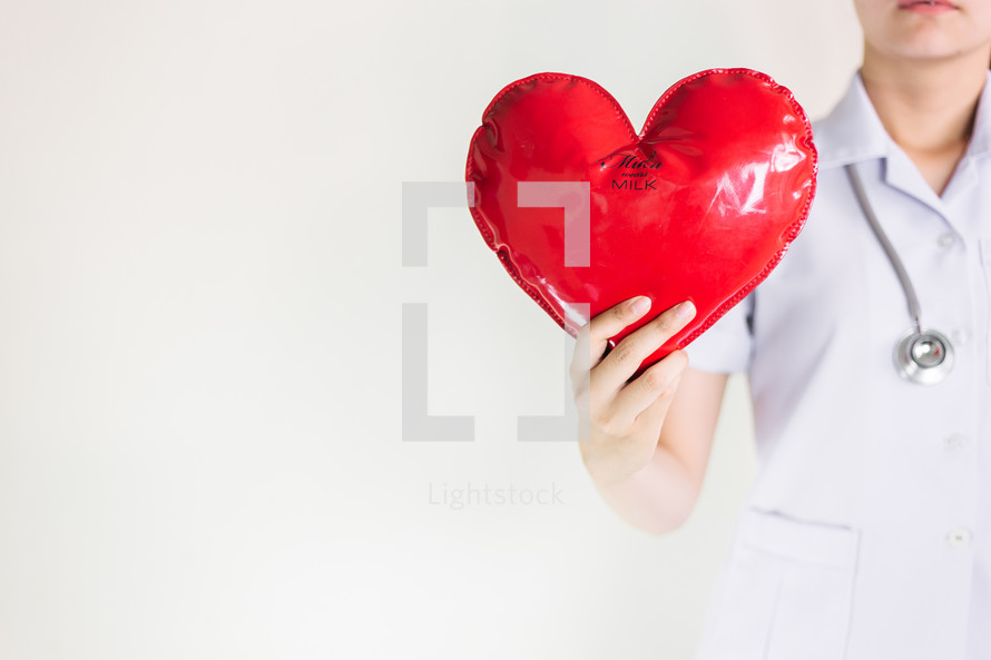 a healthcare worker holding a heart with milk