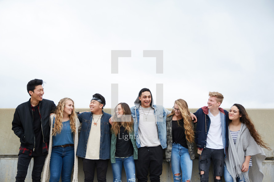 row of teens with arms around each other