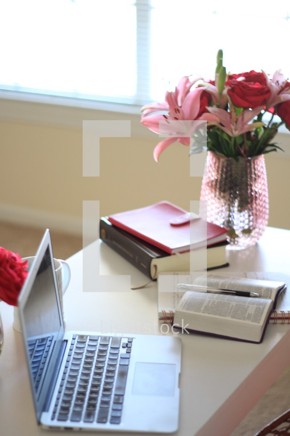 laptop computer, vase of flowers, notebook, and Bible on a desk