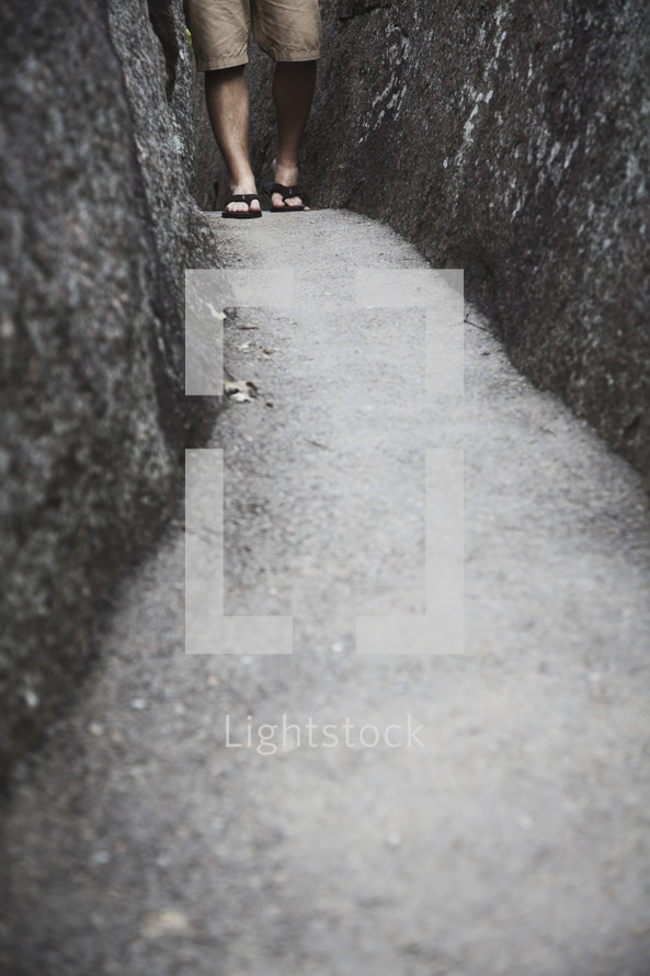 Feet in sandals walking on a paved path between two boulders.