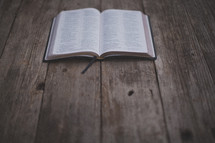 An open Bible on a wooden table