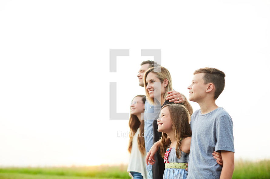 family portrait standing outdoors at sunset