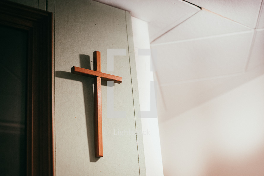 wooden cross hanging on a church wall