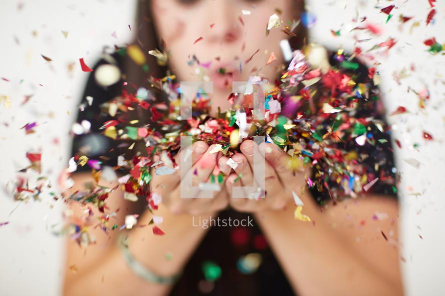 a woman blowing colorful confetti