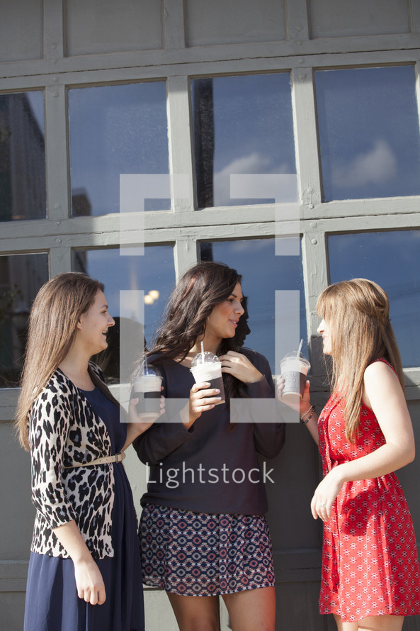Group of women holding frozen latte drinks.