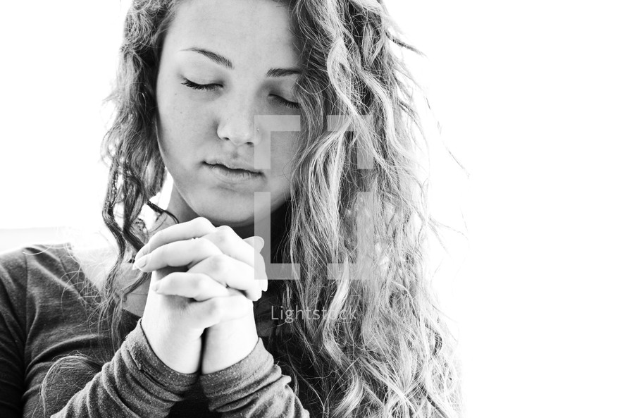 Teenage girl praying with fingers laced.