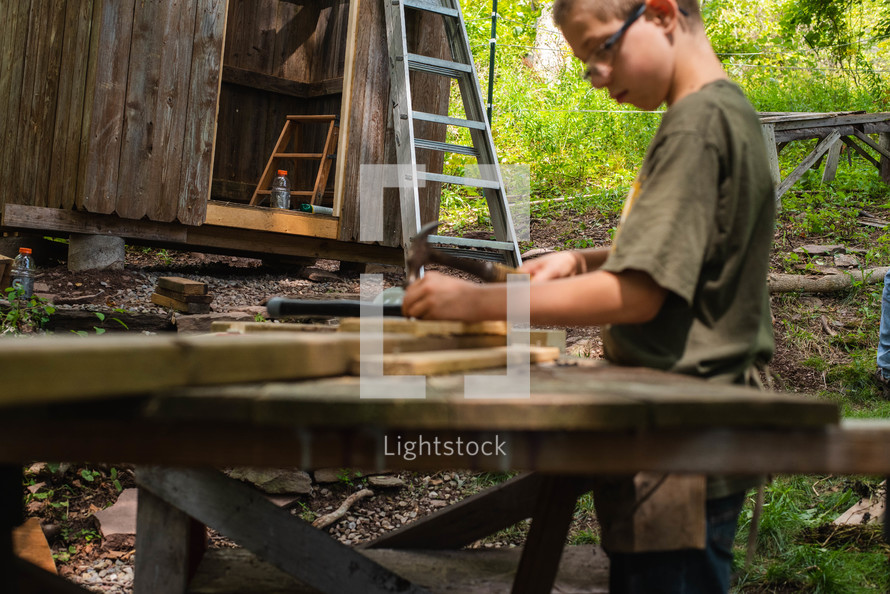 a boy hammering a nail