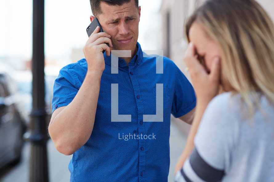 a man talking on a cellphone and a frustrated woman