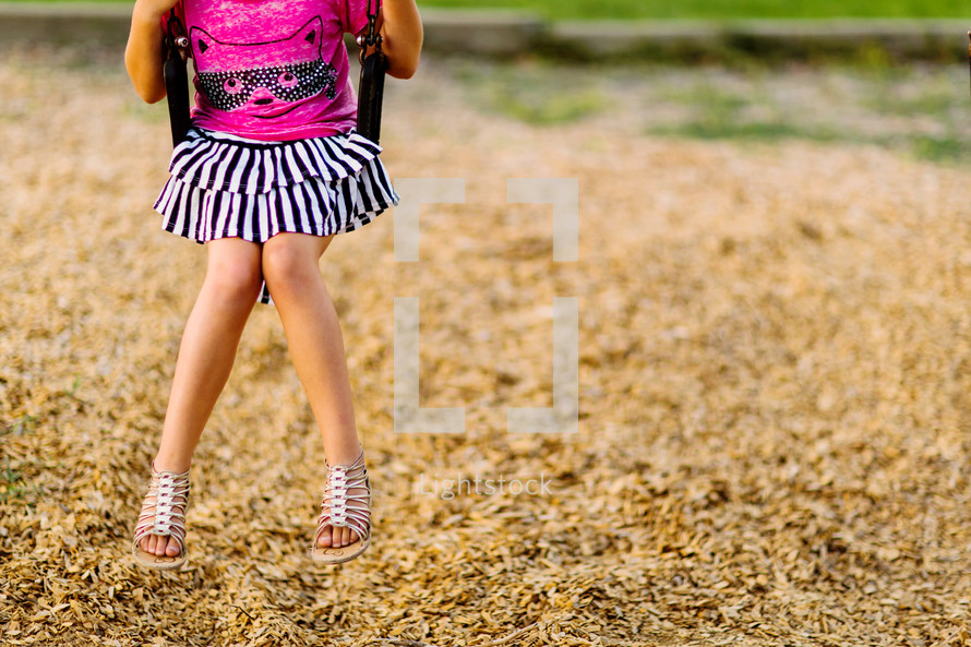 Young elementary school girl alone on a swing, playground, student, school, fatherless, children, child,
