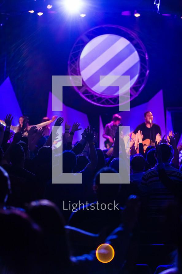 Hands raised in worship, crowd, blue, purple,