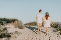 a couple walking on a beach holding hands