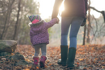 mother and toddler daughter walking in the woods in coats holding hands