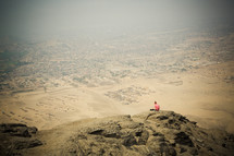 Person sitting atop a rocky mountain overlooking the desert.