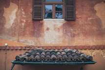 gutters, tile roof, and exterior wall with a window