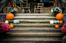 Beautiful autumn arrangement of pumpkins, flowers, gourds, wooden chairs, hay bales and tassels on wooden stairs.