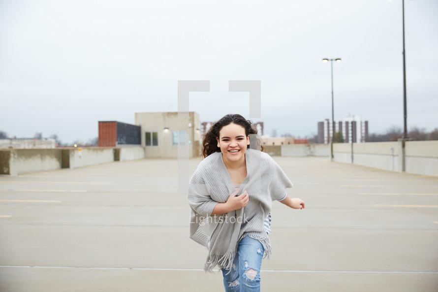 teen girl running in a parking deck