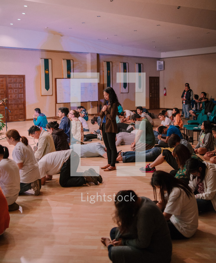 teens sitting on a floor praying during a worship service