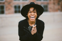 An African American woman in a black hat laughing