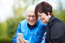 elderly couple sitting on a park bench with a cellphone