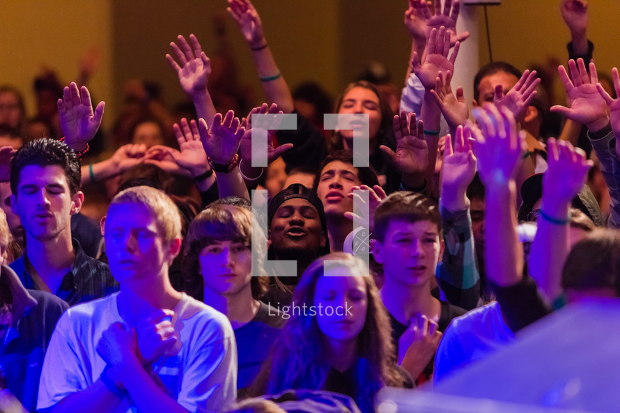 Young people, youth, teenagers in worship with hands lifted, raised hands, singing