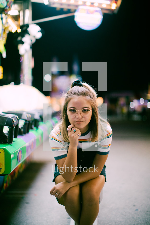 a teen girl standing next to a carnival ride