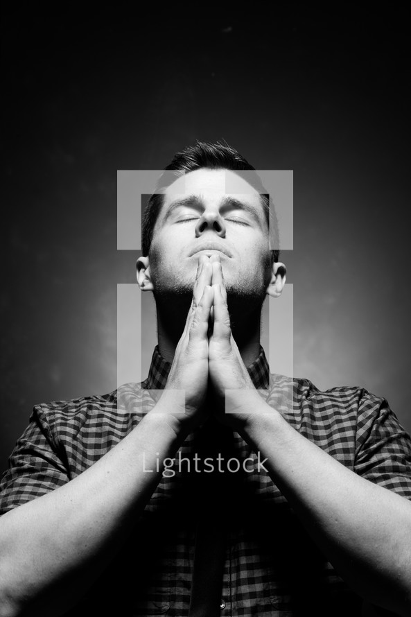 man with praying hands in prayer to God