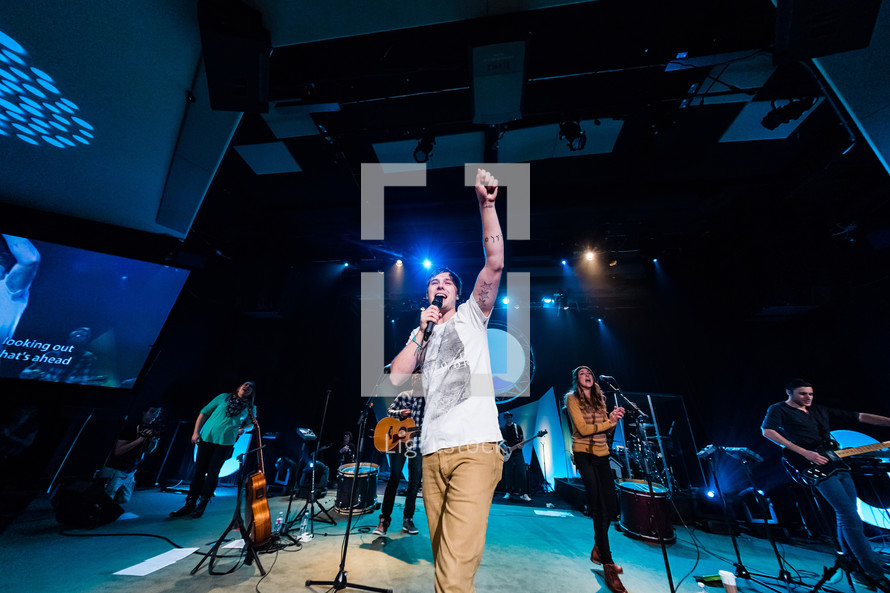 Worship leader raising fist in praise on stage, tattooed arm, youth, generation