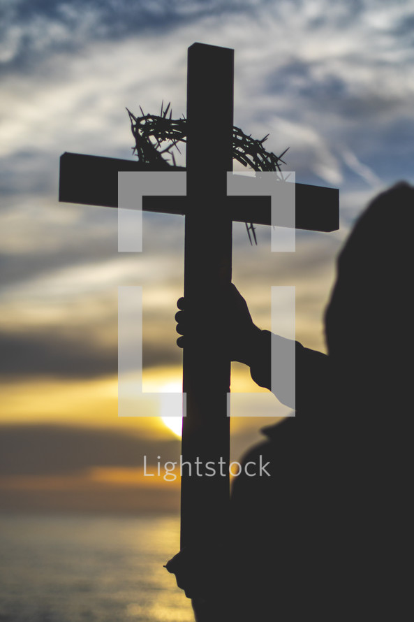 silhouette of a man holding a cross at sunset