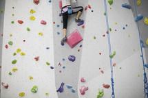 woman climbing a rock wall.