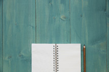 teal blue background and blank pages of a notebook