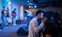 praying over another during a worship service