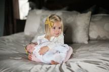 big sister holding her baby sister on a bed