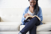 a young woman sitting on a couch reading a Bible.