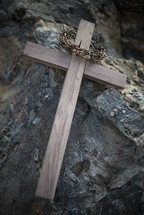 crown of thorns and wooden cross on a rock