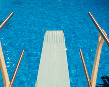 A diving board over a swimming pool.