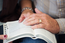 elderly couple praying over the pages of a Bible