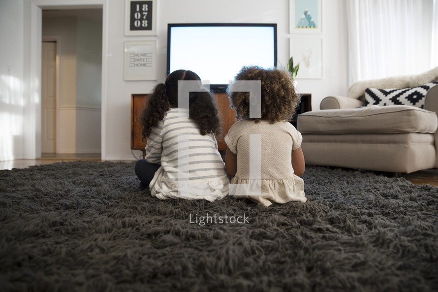 girls watching tv, sitting on a rug in a living room