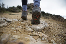 close up of person's boots hiking up a mountain.