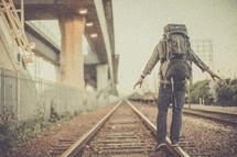 man balancing walking on railroad tracks with a backpack