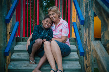 a woman hugging a girl on playground equipment