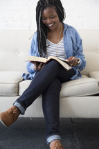 a young woman sitting on a couch reading a Bible