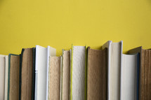 row of books against a yellow wall.