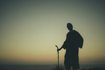 silhouette of a man in a robe and a walking stick