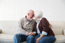 a happy, loving elderly couple snuggling on a couch