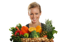 woman holding a basket of fruits and vegetables
