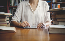 a woman sitting at a table in a library