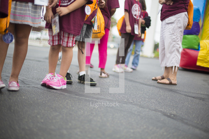 children waiting in a line to go on a jump house