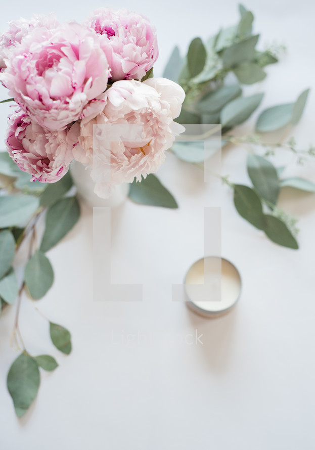 Pink peonies in  a vase surrounded by green leaves, and a votive candle on a white surface.