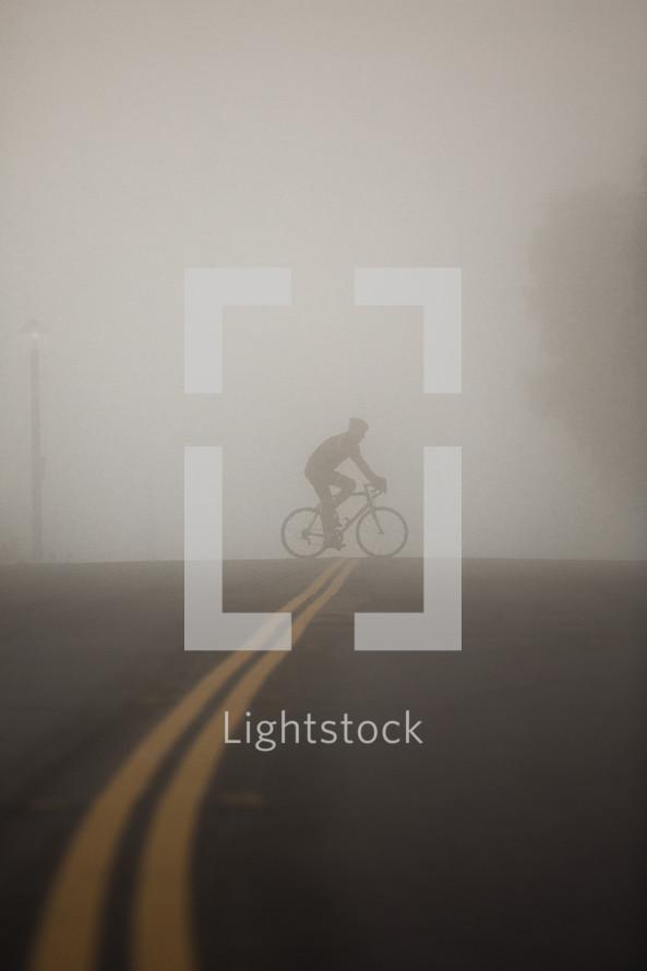 man riding a bike across the street under thick fog